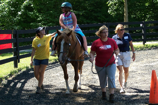 Volunteers assist a rider at Offering Alternative Therapy with Smiles (O.A.T.S.), a PATH International premier accredited center in Clarkston, Michigan.