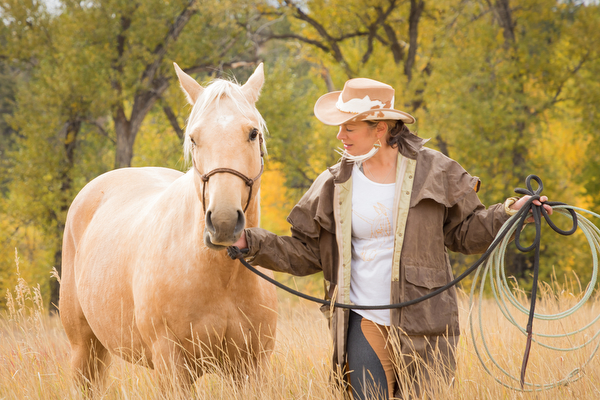 cowgirl with palomino horse in pasture