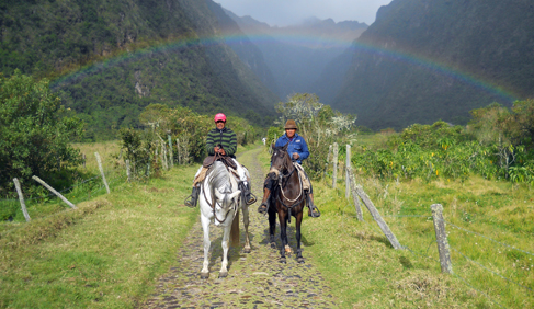 Amable and Jose horse riding with a beautiful rainbow at Hacienda Zuleta- Ecuador Riding Vacations