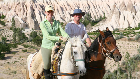 Equitrekking host Darley Newman with guide Ahmet Diler in front of the Red and Rose Valleys in Cappadocia.