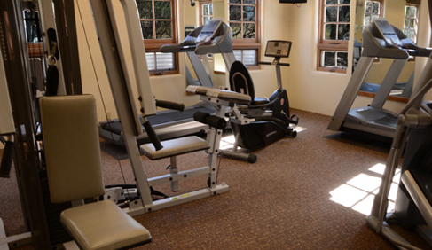 An indoor fitness center is located near the swimming pool and spa at Tanque Verde Ranch- Arizona Dude Ranch.
