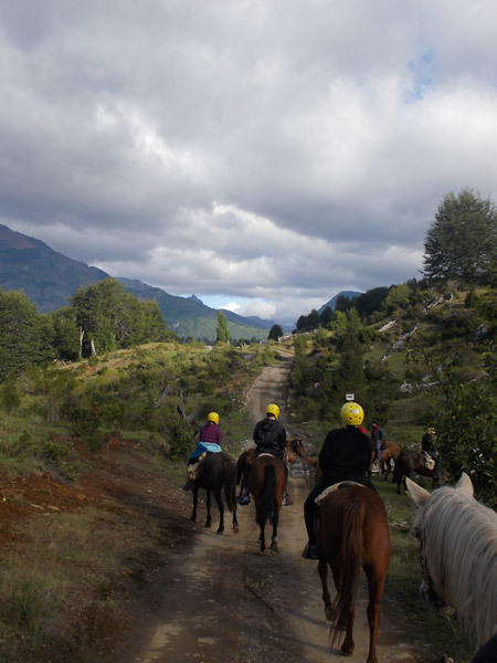 equestrians horseback riding towards the mountains in patagonia