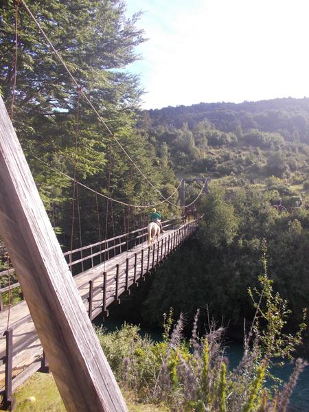 horse and rider cross swinging bridge in patagonia