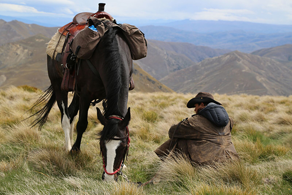 a guest takes a break from horseback riding and sits by his horse in New Zealand hosted by Adventure Horse Trekking
