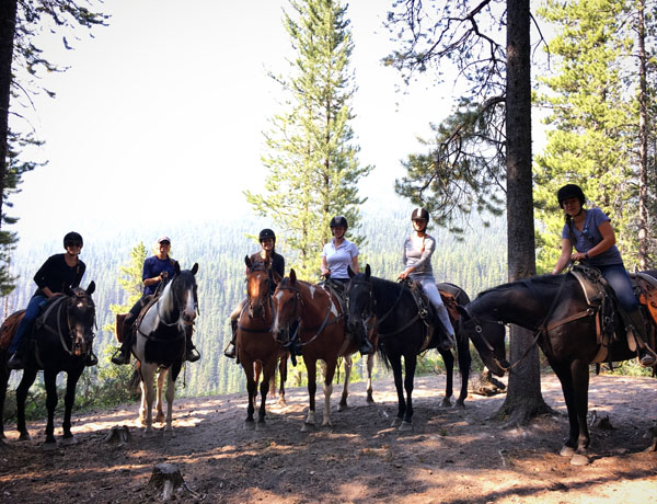 group of friends riding horses in banff national park canada