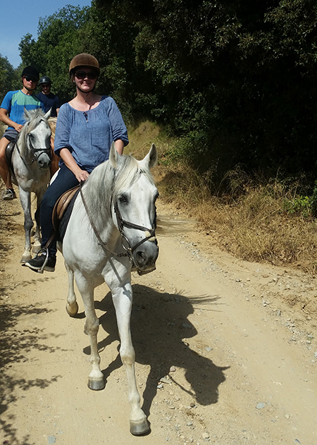 woman riding andalusian horse on trail ride in catalonia spain