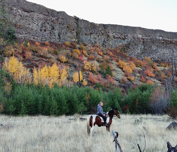 woman riding horse in canyon in the fall riverside state park washington