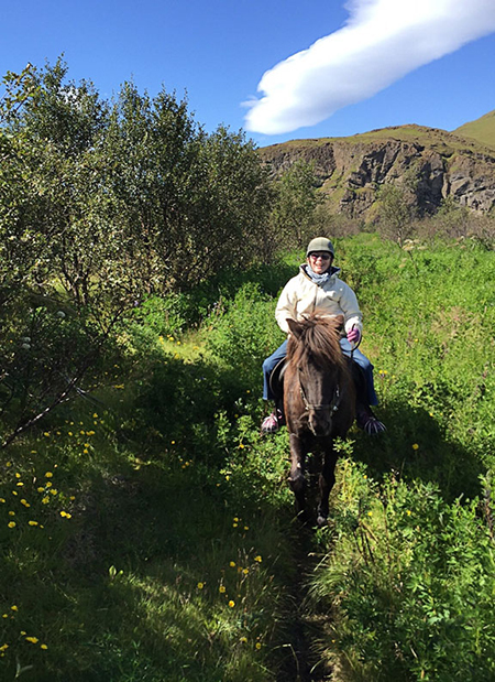 woman riding icelandic horse through trail of flowers