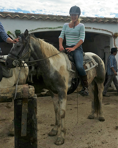 young woman riding spanish quarter horse cross in camargue france