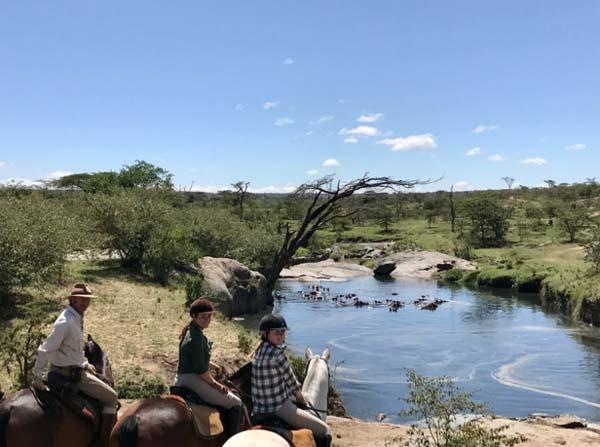 group of equestrians horseback riding on masai mara in kenya