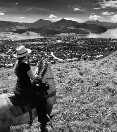 Kate riding her horse and looking down on the town of Keystone Colorado