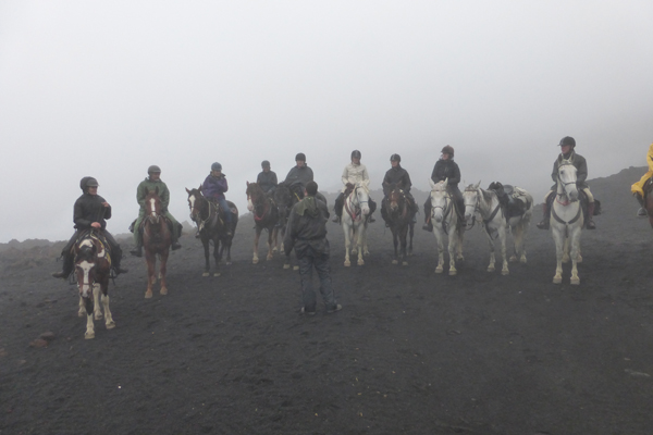 equestrians in the mist riding mount etna in sicily
