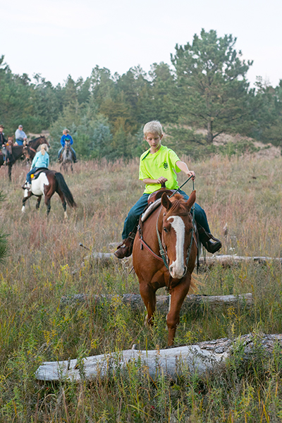 Greg leads his horse over small log obstacles in the Nebraska National Forest