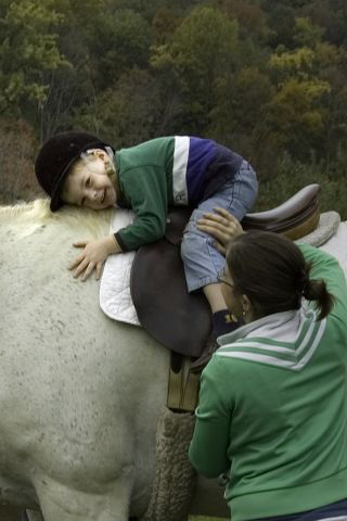 therapeutic riding boy hugging horse