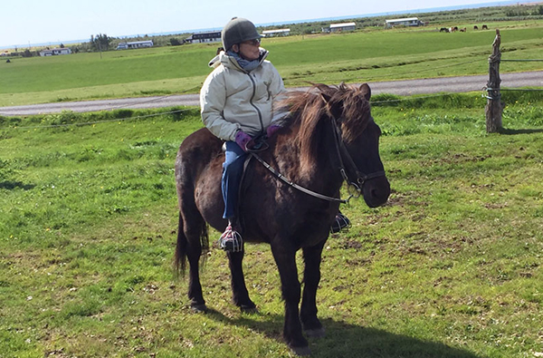 senior woman riding icelandic horse in iceland