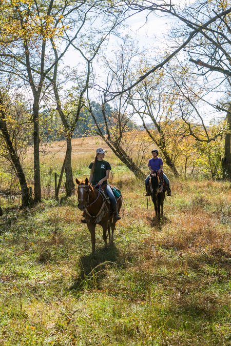 two women ride horses through fall trees in alabama