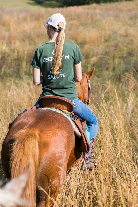 young woman rides horse through tall grass
