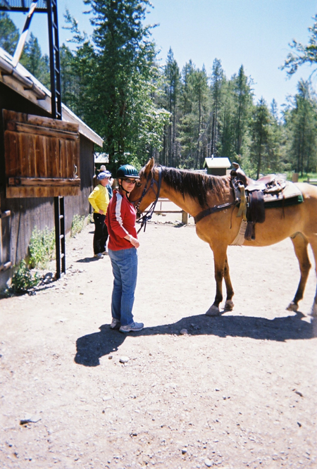 woman and horse prepare for trail ride in glacier national park in montana