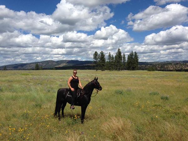 woman riding black saddlebred in riverside state park washington