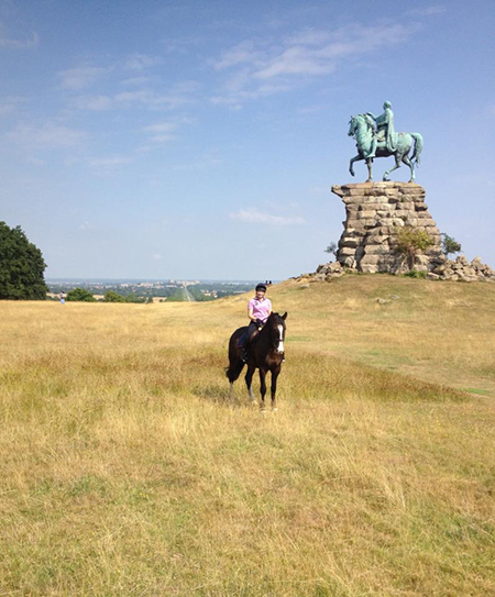 woman riding horse atop snow hill near king george the third statue in windsor great park