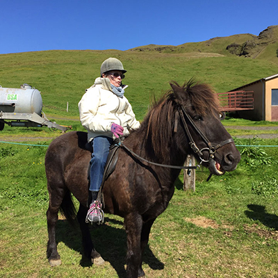 senior woman horseback riding in iceland