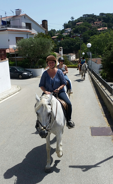 woman riding white andalusian horse through streets of orrius spain